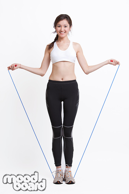 Portrait of smiling young woman exercising with skipping rope against white background