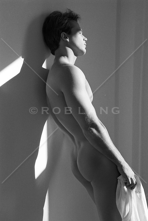 male nude leaning against a wall in sunset light