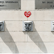 A wall sculpture of three stylized faces at the Mont des Arts in Brussels, Belgium.