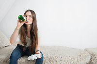 Young woman drinking beer while playing video game