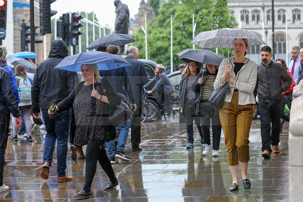 © Licensed to London News Pictures. 18/06/2019. London, UK. Tourists shelters from the rain under umbrellas in Westminster. The Met Office has issued a yellow weather warning for London as torrential rain, hail and lightning is forecasted. Photo credit: Dinendra Haria/LNP