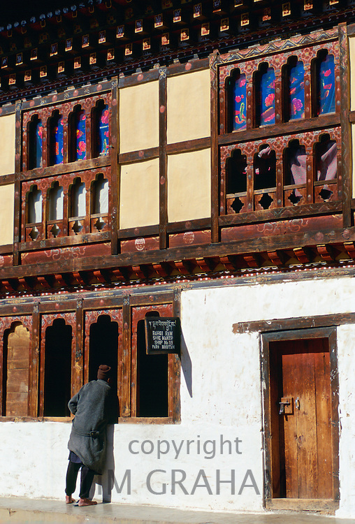 Bhutanese man removes his shoes as he leans in the open carved window of the Shoe Shop in Paro, Bhutan