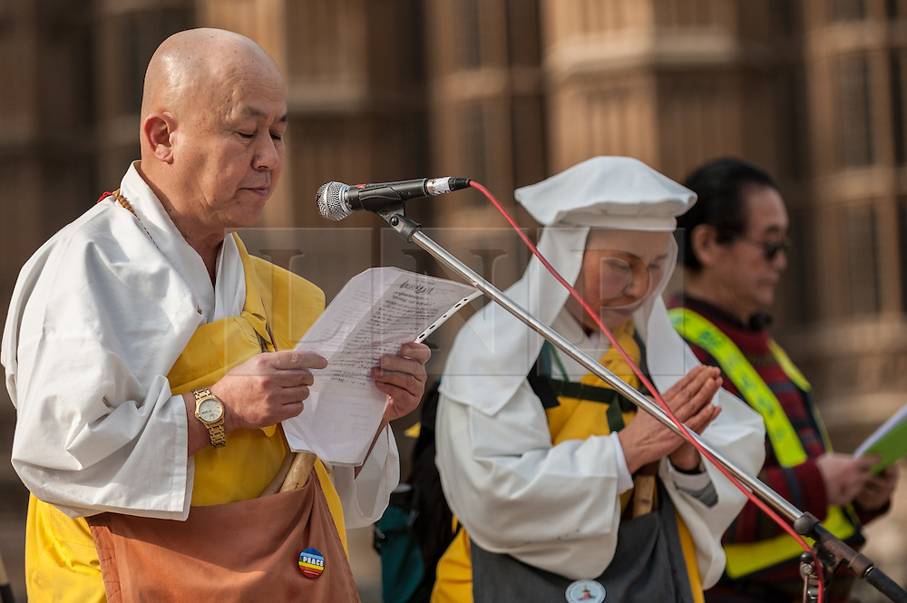 © Licensed to London News Pictures. 12/03/2016. London, UK.  Senior Buddhist monks in the UK, the Reverend Nagase and Sister Maruta, offer prayers at a rally held outside the Houses of Parliament in Westminster to recognise the fifth anniversary of the Fukushima nuclear disaster in Japan and to protest against the Japanese government's plans to restart the Sendai nuclear plant. Photo credit : Stephen Chung/LNP