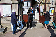 British elderly people turn up to vote in local government elections polling station in Wadebridge, North Cornwall, United Kingdom.  They are met at the entrance by a representative of the Conservative party.
