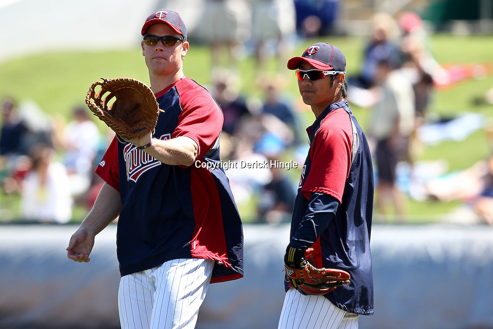 March 11, 2011; Fort Myers, FL, USA; Minnesota Twins first baseman Justin Morneau (33) and second baseman Tsuyoshi Nishioka (1) before a spring training exhibition game against the Boston Red Sox at Hammond Stadium.   Mandatory Credit: Derick E. Hingle