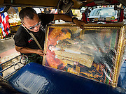 18 OCTOBER 2016 - BANGKOK, THAILAND: A tuk-tuk (three wheeled taxi) driver slides a portrait of Bhumibol Adulyadej, the King of Thailand, into his tuk-tuk. King Bhumibol Adulyadej died Oct. 13, 2016. He was 88. His death came after a period of failing health. Bhumibol Adulyadej was born in Cambridge, MA, on 5 December 1927. He was the ninth monarch of Thailand from the Chakri Dynasty and is also known as Rama IX. He became King on June 9, 1946 and served as King of Thailand for 70 years, 126 days. He was, at the time of his death, the world's longest-serving head of state and the longest-reigning monarch in Thai history.     PHOTO BY JACK KURTZ