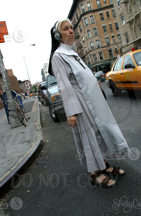 Aug 16, 2002; New York, NY, USA; A Catholic Nun walks across 7th Ave in Greewich Village with headphones on her head while wearing her gown.  Mandatory Credit: Photo by Shelly Castellano/ZUMA Press. (©) Copyright 2002 by Shelly Castellano