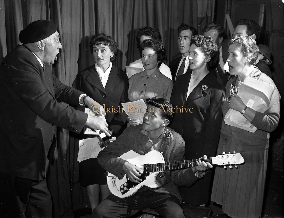 "11/09/1961<br /> 09/11/1961<br /> 11 September 1961<br /> Rehearsal for ""Sceal ar Phadraig"" new play at Damer Hall by Sean O'Tuama.  Special for Gael Linn. Alf MacGabhann, director of the Municipal School of Music Choir is on the left. His son George is playing the guitar."