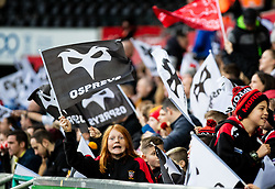 Ospreys fans wave their flags<br /> <br /> Photographer Simon King/Replay Images<br /> <br /> Guinness PRO14 Round 11 - Ospreys v Scarlets - Saturday 22nd December 2018 - Liberty Stadium - Swansea<br /> <br /> World Copyright © Replay Images . All rights reserved. info@replayimages.co.uk - http://replayimages.co.uk