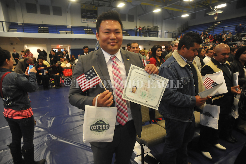 Sung Ra receives his citizenship papers following a Naturalization Ceremony in U.S. District Court for the Northern District of Mississippi, at Oxford High School in Oxford, Miss. on Tuesday, November 18, 2014. The ceremony was the first the court has ever held at the school.