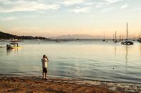 Homem fotografando a paisagem na Praia de Santo Antonio de Lisboa. Florianópolis, Santa Catarina, Brasil. / Man photographing the landscape at Santo Antonio de Lisboa Beach. Florianopolis, Santa Catarina, Brazil.