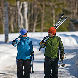 A couple carries their cross-country skis at Medawisla Wilderness Camps near Greenville, Maine.