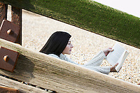 Young woman reading book sitting behind wooden balustrade on beach