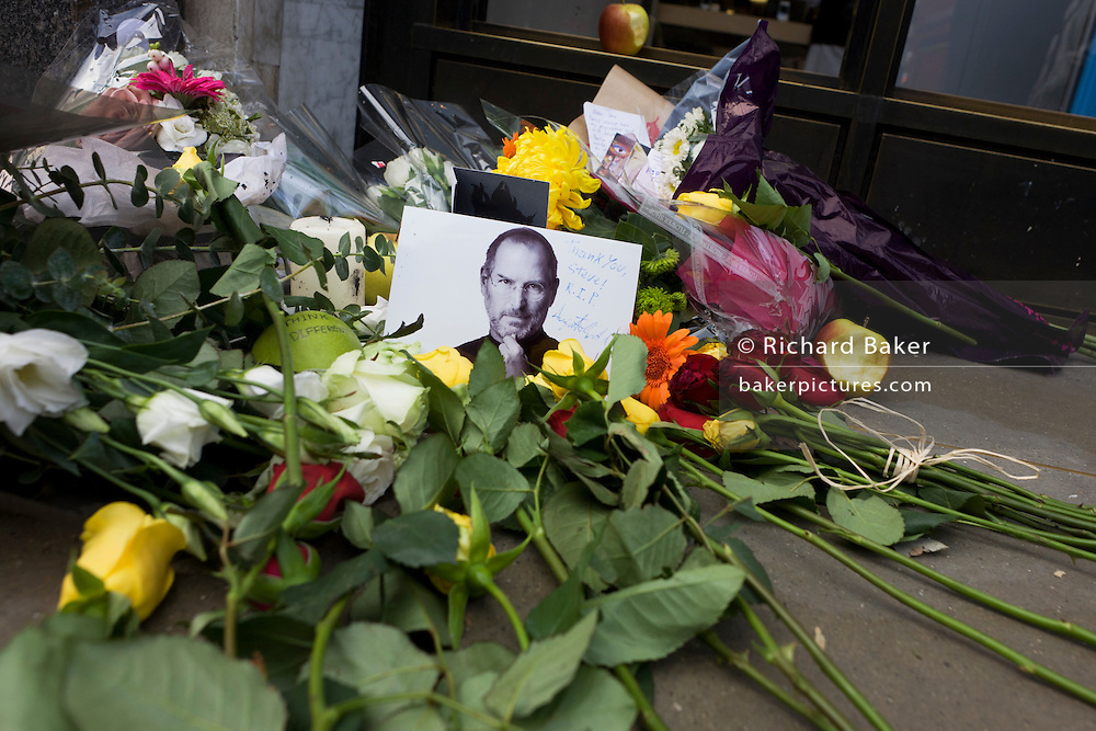 A detail portrait of Apple's creator Steve Jobs at a  makeshift shrine, where Londoners commemorate the morning after hearing of his death overnight from pancreatic cancer  at the age of 56 on the 6th Oct 2011. This Apple Store in the capital's Regent's Street was the first to be built in Europe and serves as a flagship outlet for the stylish brand of computer accessories that were largely the brainchild of Jobs who started the company as a student in 1977.