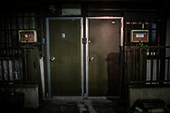 Neighbors behind side by side fake wood doors.  Hatagaya, Tokyo, Japan.