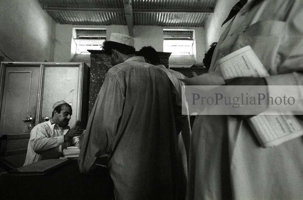 A Pakistani Customs Officer issues visas to travelers at the Torkhan frontier's post