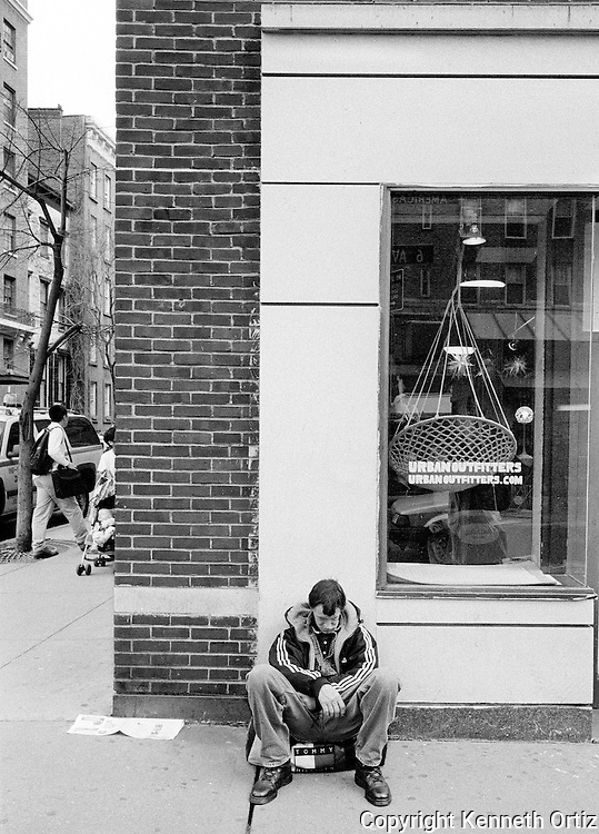 A young man sitting on his bag on 6th Avenue in the village.