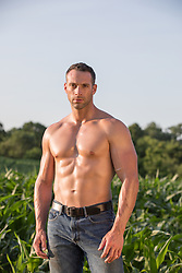 shirtless muscular man standing in a field