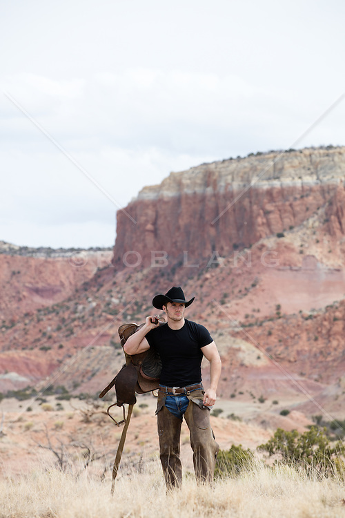 cowboy with a saddle on a mountain range