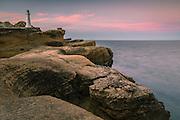 Sunset at Castlepoint Lighthouse, along a rocky limestone cliff.  Wairarapa, North Island, New Zealand.