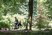 Bij Rhijnauwen fietst een jonge moeder met een kind achterop de fiets. Veel mensen genieten  van het mooie weer, door te wandelen, te fietsen of een pannenkoek te eten bij het pannenkoekenrestaurant.<br /> <br /> Near Rhijnauwen a young mother is cycling with a child at the back seat. People are enjoying the nice weather by walking, cycling or eating pancakes.