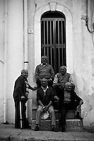 Un gruppo di amici anziani seduti sulle scale di una casa di fine '800