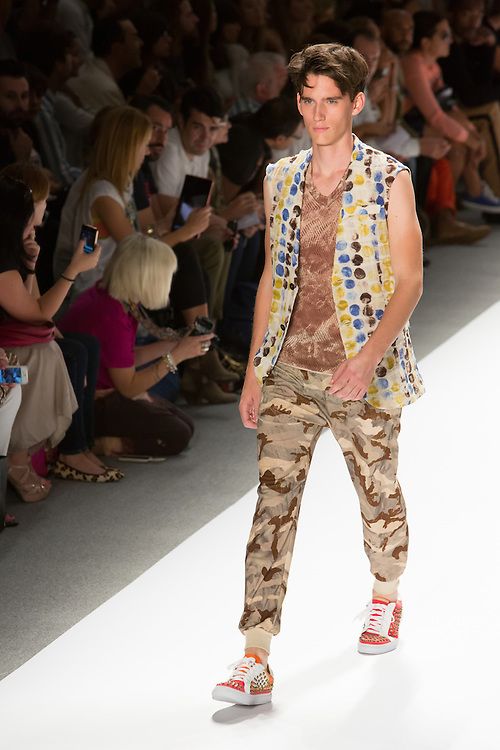 Men's camo print pants, V-neck print T and white, yellow, blue and black vest. By Custo Barcelona at the Spring 2013 Fashion Week show in New York.