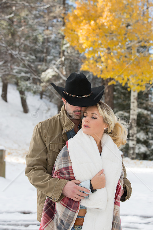 cowboy and a girl wrapped in a blanket outdoors in the snowy woods