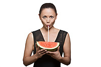 Portrait of beautiful Asian woman drinking juice through watermelon in studio isolated on white background