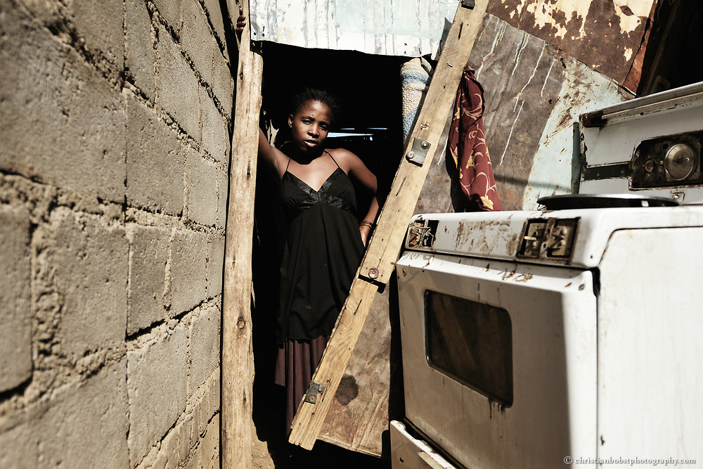Sixteen-year-old Winnie stands in the entrance of the hut that she and two roommates have rented. Often, the girls are sought out and sexually assaulted by unknown men in the hut, particularly when they are drunk and defenseless. They can't protect themselves because the door has no hinge and no lock.