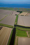 Nederland, Groningen, Oldambt, 08-09-2009; Hoofdkanaal gezien naar de coupure en sluis in de dijk van de Reiderwolderpolder, boven in beeld de Carel Coenraadpolder, ontstaan door landaanwinning in de Dollard. Emden met windmolens aan de verre horizon.Main watring canal seen in direction of the cut and lock in the dike of the Reiderwolderpolder, top of the photo the Carel Coenraad polder, created by land reclamation in the Dollard.luchtfoto (toeslag); aerial photo (additional fee required); .foto/photo Siebe Swart
