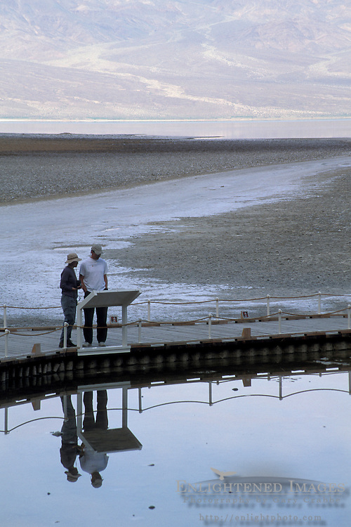 Tourists looking into saltwater pools from boardwalk at Badwater, Death Valley National Park, California