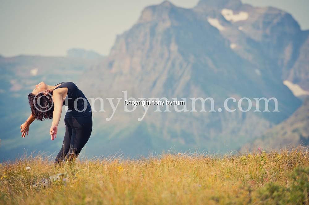 woman performs yoga on a grassy ridge with huge mountain backdrop, glacier national park