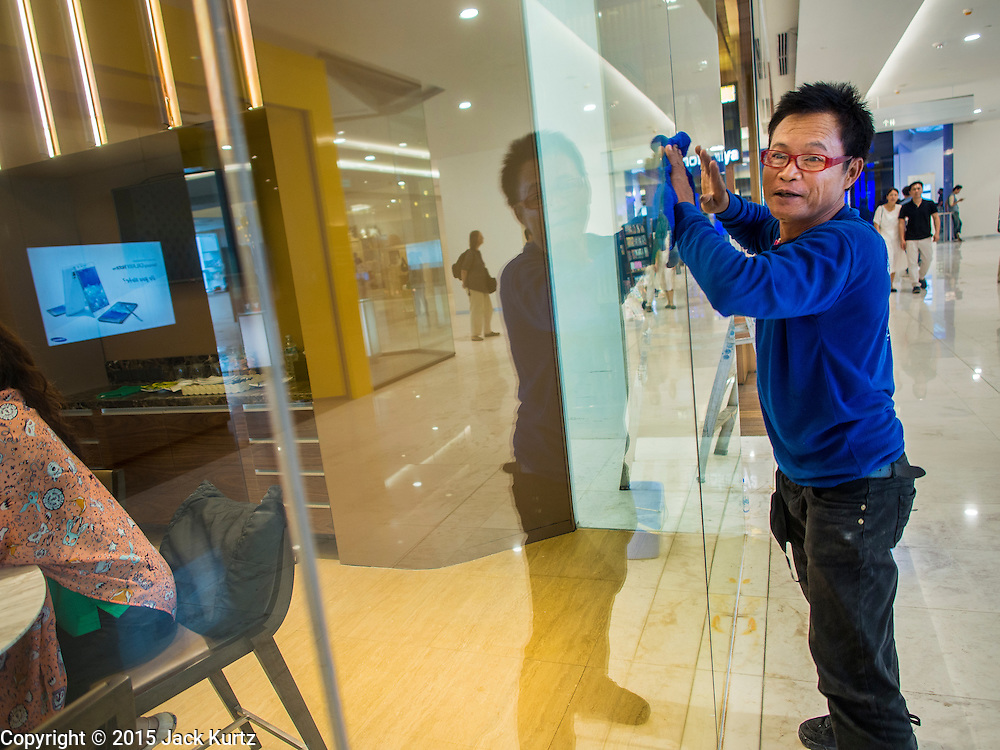 "27 MARCH 2015 - BANGKOK, THAILAND: A worker cleans a window in a bank in ""EmQuartier,"" a new mall in Bangkok. ""EmQuartier"" is across Sukhumvit Rd from Emporium. Both malls have the same corporate owner, The Mall Group, which reportedly spent 20Billion Thai Baht (about $600 million US) on the new mall and renovating the existing Emporium. EmQuartier and Emporium have about 450,000 square meters of retail, several hotels, numerous restaurants, movie theaters and the largest man made waterfall in Southeast Asia. EmQuartier celebrated its grand opening Friday, March 27.    PHOTO BY JACK KURTZ"