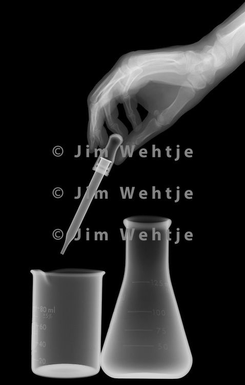 X-ray image of science glassware with hand (white on black) by Jim Wehtje, specialist in x-ray art and design images.