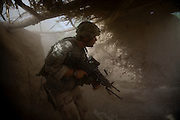 Private Dan Burris of the 82nd Airborne's, 1/508 PIR, Alpha Company, Third Platoon searches a compound throught the dust and smoke of a grenade near Sangin, Helmand province, Afghanistan on Wednesday, April 11, 2007/