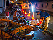 "27 MARCH 2013 - BANGKOK, THAILAND:  Men work at upgrading sewer lines in a residential neighborhood in Bangkok. Thailand's economic expansion since the 1970 has dramatically reduced both the amount of poverty and the severity of poverty in Thailand. At the same time, the gap between the very rich in Thailand and the very poor has grown so that income disparity is greater now than it was in 1970. Thailand scores .42 on the ""Ginni Index"" which measures income disparity on a scale of 0 (perfect income equality) to 1 (absolute inequality in which one person owns everything). Sweden has the best Ginni score (.23), Thailand's score is slightly better than the US score of .45.  PHOTO BY JACK KURTZ"