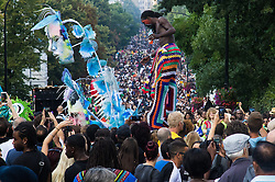 London, August 29th 2016. A dancer on stilts rises above the vast crowd on Ladbroke Grove during day two of Europe's biggest street party, the Notting Hill Carnival.