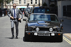 A stunt double stands beside an Aston Martin as filming for the upcoming Bond film takes place on the Mall in London. The as-yet-untitled project has been shooting in Jamaica and at Pinewood Studios but the official 007 Twitter account confirmed the spy movie is now filming in the capital.
