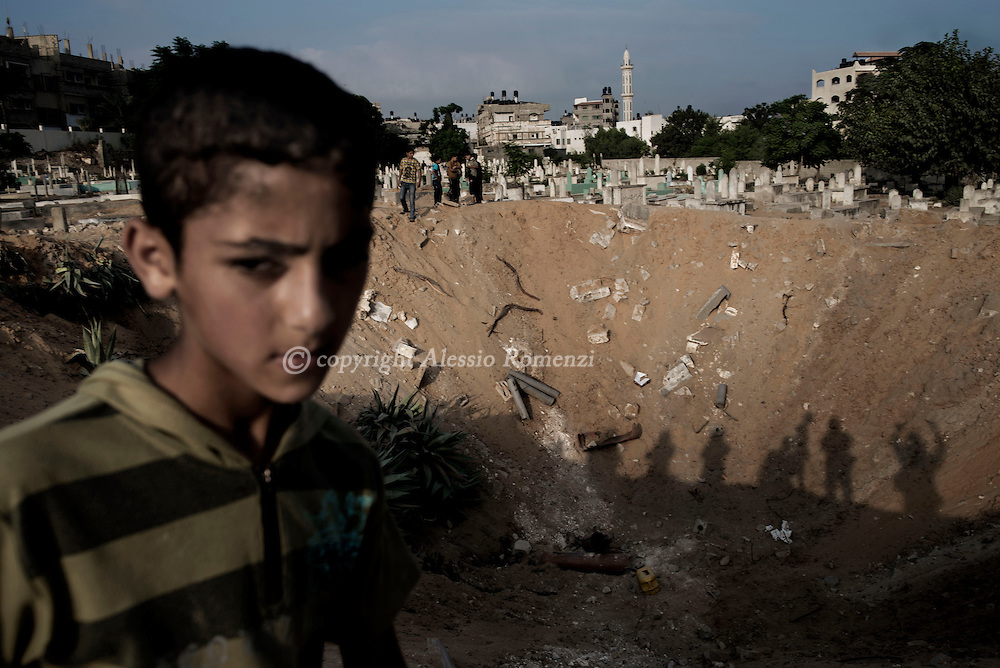 Gaza Strip, Jabalyia: A Palestinian child stands on the edge of the crater left by an Israeli airstrike on Jabalyia refugee camp cemetery, few kilometres north of Gaza City on July 28, 2014. ALESSIO ROMENZI