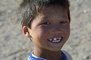 GOBI DESERT, MONGOLIA..08/31/2001.Tsagan Bulag, kid with broken teeth at gers belonging to the family of 15-year-old Urna, winner of a gold medal in an English language school competition..(Photo by Heimo Aga).