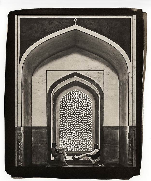 Two men having a conversation while sitting on the ground in Humayan's Tomb in Delhi, India are framed by an arch built in the classic architectural lines of the Mughal style.