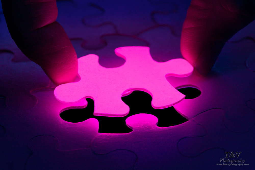 The last glowing piece of a jigsaw puzzle is put into its place. Blacklight photography.