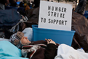 "A man with his eyes closed lies down in front of a sign reading ""Hunger strike to support."""