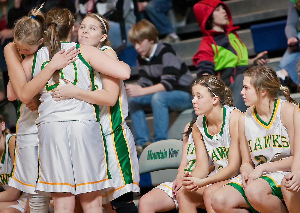 JEROME A. POLLOS/Press..Lakeland High's Kristyn App, left, and Breezy Stecker hug teammate Katie Imthurn after she came off the court to join Kerstyn Reed, right, and Emily Stecker on the bench in the closing seconds of the Hawk's 69-52 loss to Jerome High in the 4A state championship tournament consolation game held Saturday in Meridian.