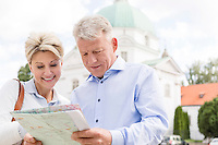 Smiling middle-aged couple reading map outdoors