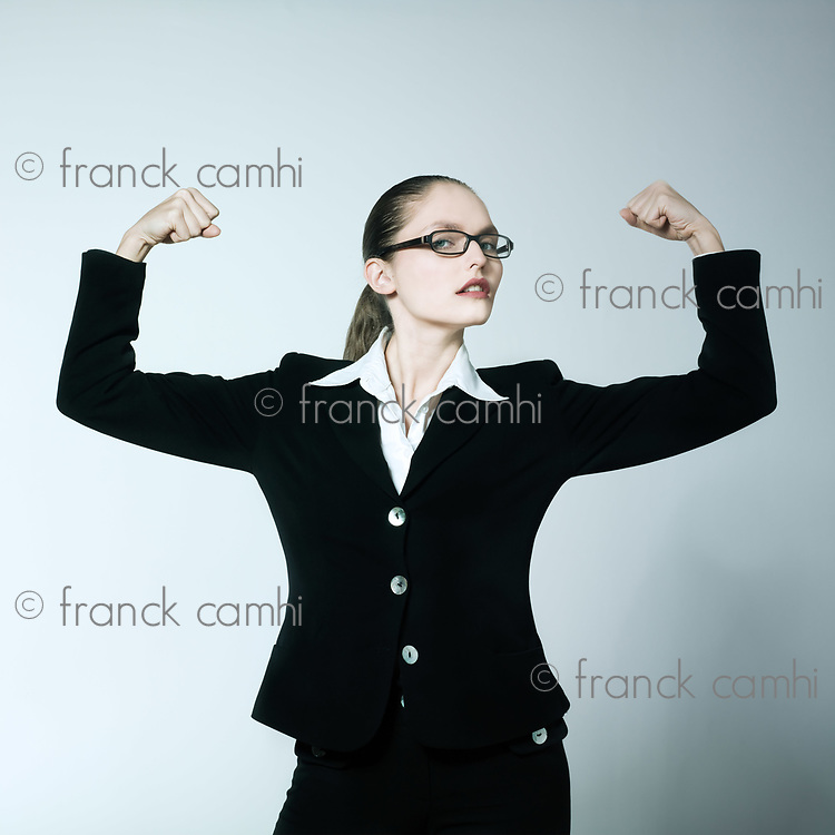 studio shot portrait of a beautiful young woman in a costume suit feeling strong