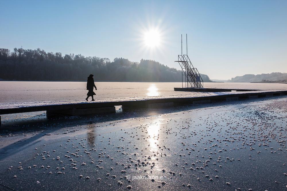 Woman walking on wooden jetty. Frozen Lake in Viljandi, Estonia. Diving tower, winter, sun.