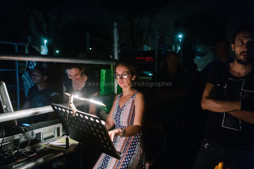 ROME, ITALY - 27 JUNE 2017: Assistant director Martina Santese checks the Don Giovanni score during the performance of &quot;Don Giovanni OperaCamion&quot;, an open-air opera performed on a truck in San Basilio, a suburb in Rome, Italy, on June 27th 2017.<br /> <br /> Director Fabio Cherstich&rsquo;s idae of an &ldquo;opera truck&rdquo; was conceived as a way of bringing the musical theatre to a new, mixed, non elitist public, and have it perceived as a moment of cultural sharing, intelligent entertainment and no longer as an inaccessible and costly event. The truck becomes a stage that goes from square to square with its orchestra and its company of singers in Rome. <br /> <br /> &ldquo;Don Giovanni Opera Camion&rdquo;, after &ldquo;Don Giovanni&rdquo; by Wolfgang Amadeus Mozart is a new production by the Teatro dell&rsquo;Opera di Roma, conceived and directed by Fabio Cherstich. Set, videos and costumes by Gianluigi Toccafondo. The Youth Orchestra of the Teatro dell&rsquo;Opera di Roma is conducted by Carlo Donadio.