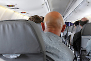 back of a bald shaven head of man sitting in airplane